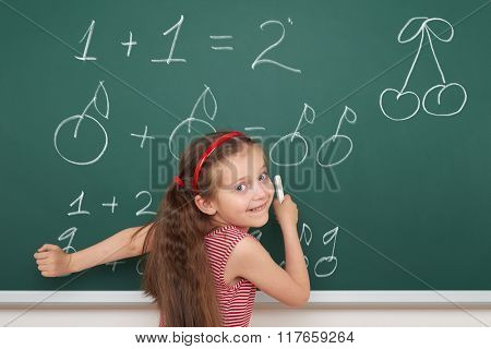 school girl exercise math from fruits on board