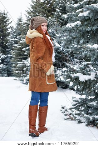 Girl walk in winter park at day. Snowy fir trees. Redhead woman full length.