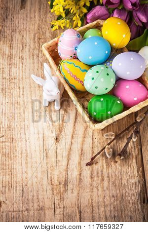 Easter still life with basket eggs rabbit and bunch spring flowers on wooden board