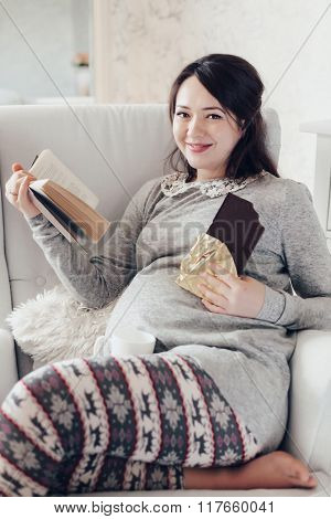 Home cozy portrait of pregnant woman resting at home on a chair, reading a book and eating chocolate