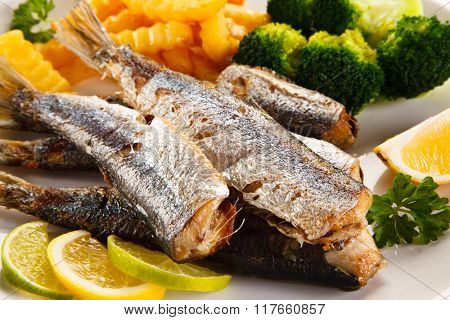 Fried herrings, chips and vegetables