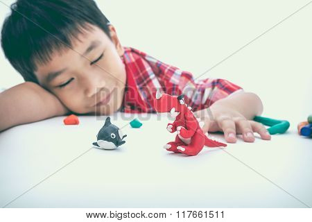 Child Sleeping With His Works From Clay, On White. Strengthen The Imagination