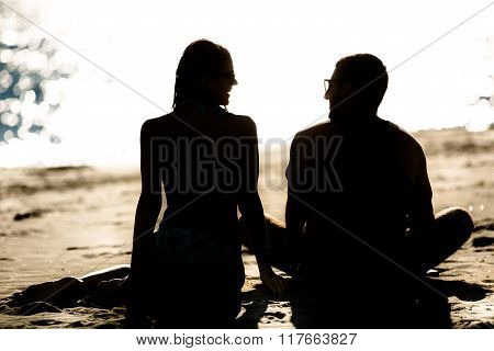 Silhouette of a couple in love on the beach at sunset