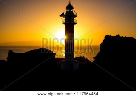 Coastline with lighthouse silhouette