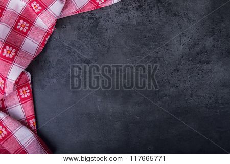 Top view of checkered kitchen tablecloth on granite - concrete - stone background. Free space