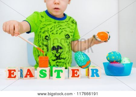 child paints the Easter eggs