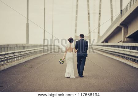 Happy bride and groom celebrating wedding day. Married couple going away on bridge. Long family life