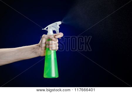 Cleaning The House And Cleaner Theme: Man's Hand Holding A Green Spray Bottle For Cleaning On A Dark