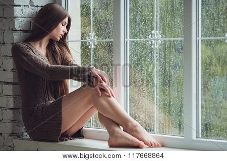 Beautiful young woman sitting alone near window with rain drops. Sexy and sad girl. Concept of lonel