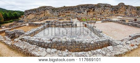 Roman ruins of Conimbriga. View of the Skeletons Domus. In the back the Defensive Wall of the city. Conimbriga, in Portugal, is one of the best preserved Roman cities on the west of the empire.