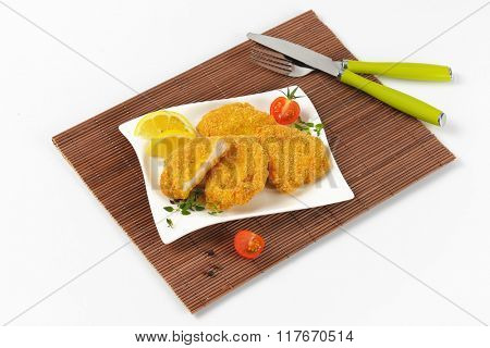 plate of breaded turkey breast on brown place mat