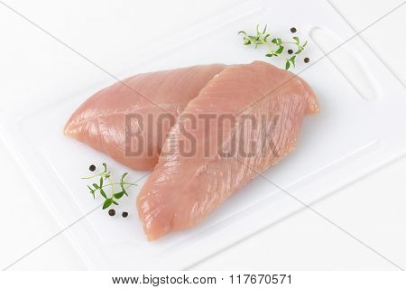 raw turkey breasts with spice and herbs on white plastic cutting board