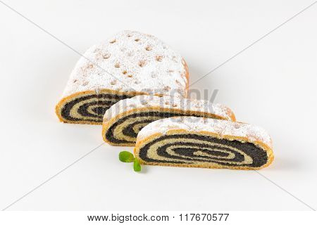 sliced poppy seed roll on white background