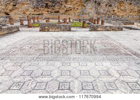 Swastikas decorating the Roman mosaics at the House of the Swastika. Defensive Wall seen in back. Conimbriga, in Portugal, is one of the best preserved Roman cities on the west of the empire.