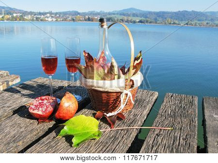 Pair of winglasses, pomegranate and autumn leaves against a lake