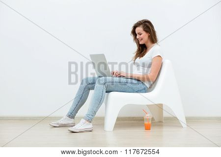Single Woman Sitting On White Chair With Laptop