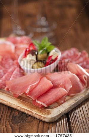 meat platter of Cured Meat and olives on old wooden board