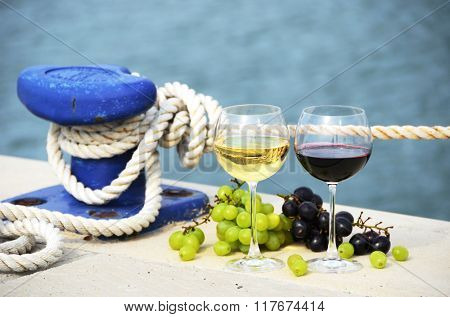 Pair of wineglasses and grapes on the pier