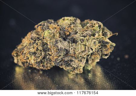 Dried weed bud over chromed surface
