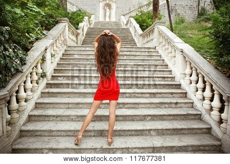 Beautiful Young Brunette Girl Model In Red Dress Posing On Staircase In Birth Of Our Lady Church, Mo