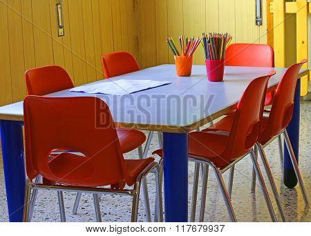 Kindergarten With Red Chairs And Small Desks And Lots Of Colored Pencils