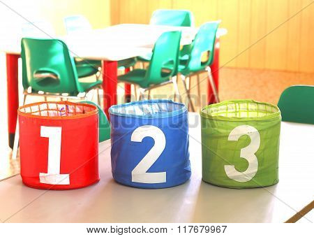 Cans With Numbers On The Desk In The Kindergarten