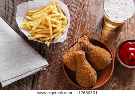 fried chicken leg in breadcrumbs and french fries