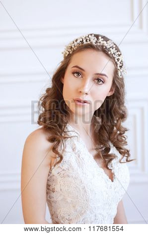 Tender Young Bride With Curly Brown Hair, White Gown And Pearl Headpiece