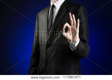 Businessman And Gesture Topic: A Man In A Black Suit And White Shirt Showing Okay Hand Sign On A Dar