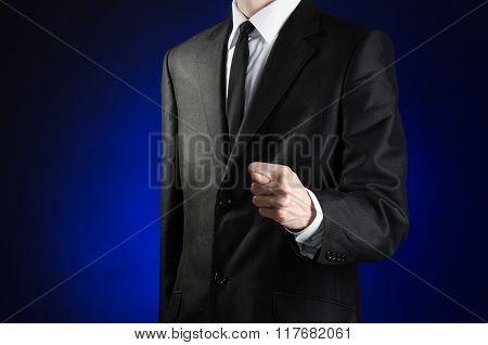 Businessman And Gesture Topic: A Man In A Black Suit And White Shirt Showing Fig Hand On A Dark Blue