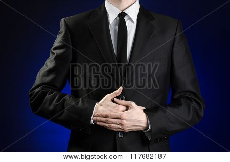 Businessman And Gesture Topic: A Man In A Black Suit And A White Shirt Holding Hands On The Sick Bel