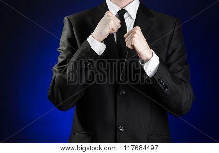 Businessman And Gesture Topic: A Man In A Black Suit And White Shirt Holding His Fists In Front Of H
