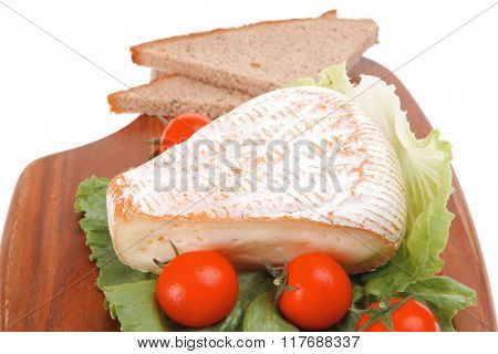 cheese served on wood with bread and tomatoes