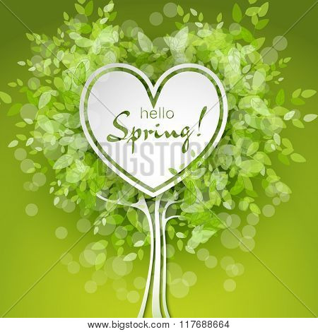 Heart shaped frame on tree background with green leaves. Hello spring