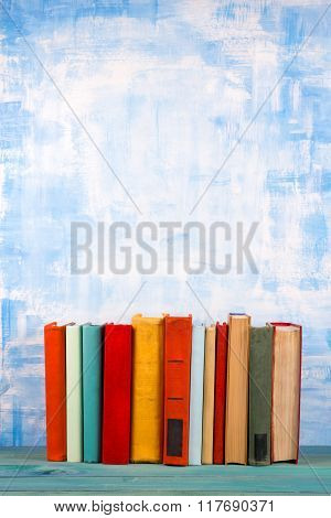 Composition with old vintage colorful hardback books, diary on w