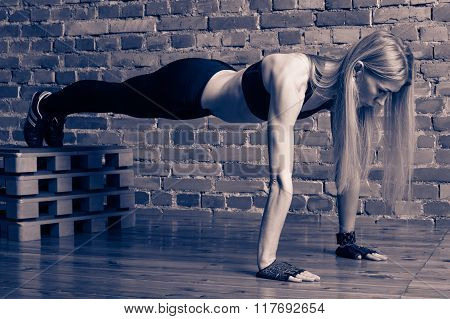 Motivation - Attractive blond fitness model performing planck exercise with a box at the gym