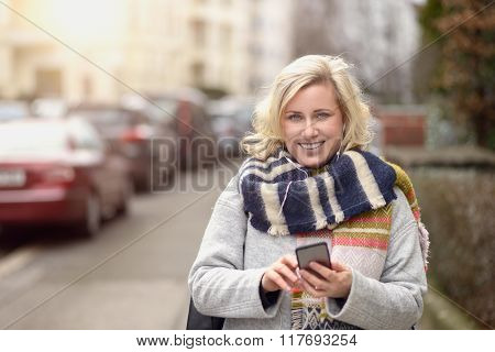 Attractive Woman Checking Her Mobile In A Street