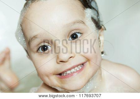 Pretty girl is taking a bath with a foam