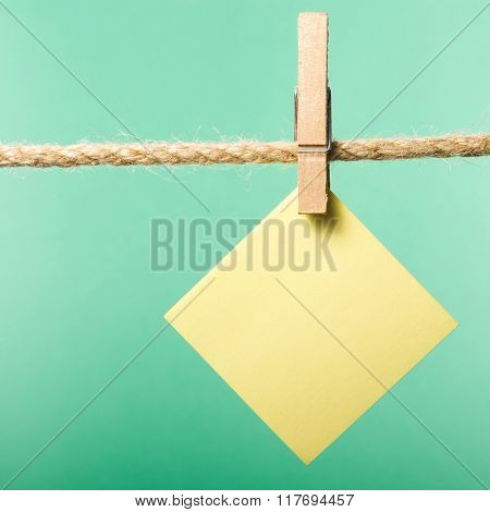 Blank paper notes hanging on rope with clothes pins, copy space