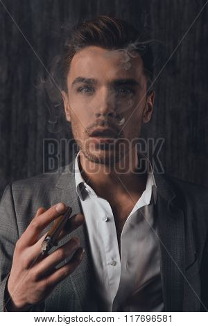Handome Sexy Man In Suit On The Grey Background Smoking A Cigar