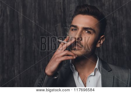 Portrait Of A Cheeky Man In Suit On The Grey Background Smoking A Cigarette