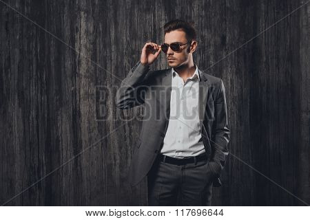 Handsome Cheeky Man With Glasses Holding Hand In A Pocket On The Grey Background