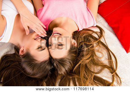 Cheerful Girls In Pajamas Gossiping And Lying On The Bed