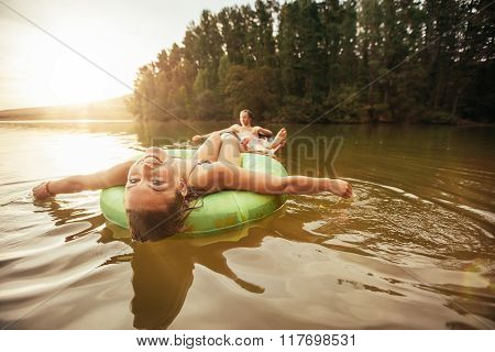 Young Woman In Lake On Inflatable Rings.