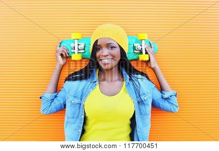 Fashion Pretty Young Smiling African Woman With Skateboard In Colorful Clothes Over Orange Backgroun