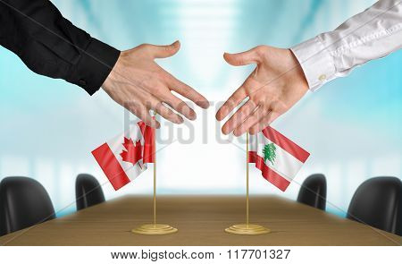 Canada and Lebanon diplomats shaking hands to agree deal