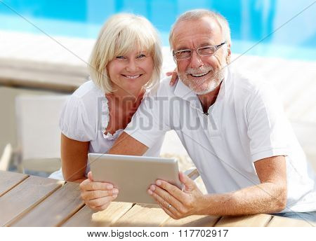 Different Aged Couple Using A Tablet Pc