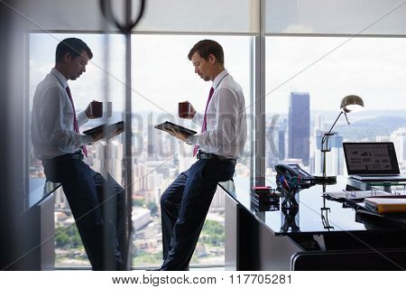 Business Person Drinks Coffe And Reads News On Tablet