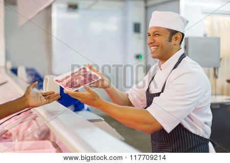 happy middle aged butcher serving customer in butchery