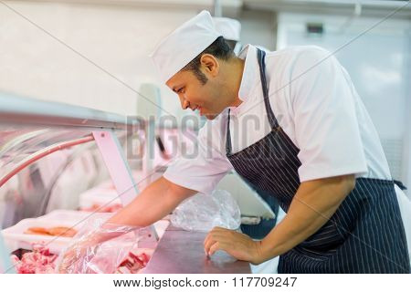 good looking butcher picking piece of meat